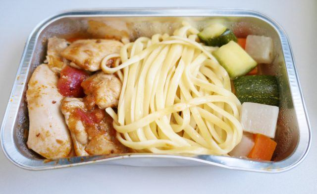 An airplane meal of chicken, pasta, and vegetables