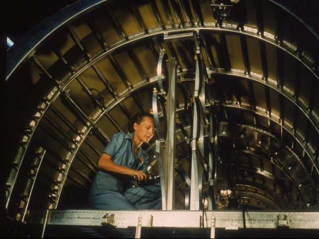 An unidentified Consolidated Aircraft Corporation employee works on a C-87 Liberator Express transport plane