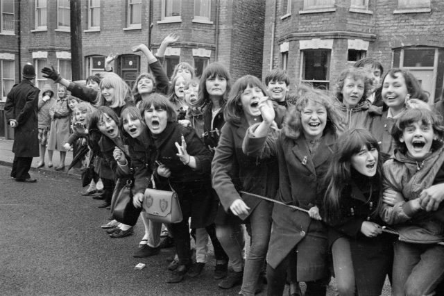 British police hold back excited young Beatles fans