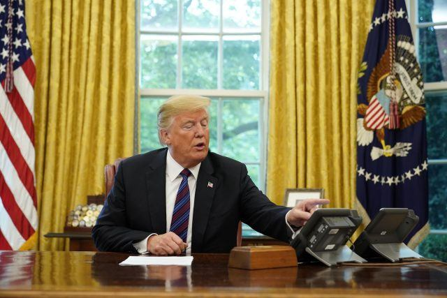 Donald Trump looks at his telephone from the Oval Office