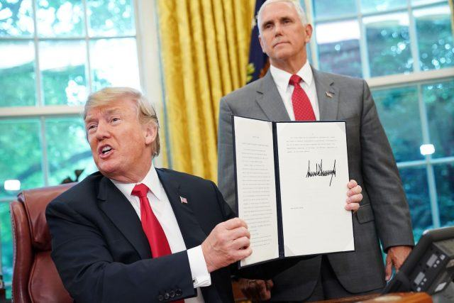 Donald Trump shows an executive order on immigration