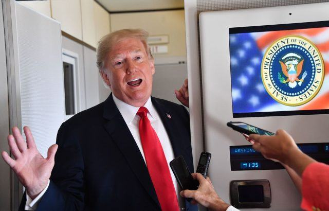Donald Trump speaks to the press aboard Air Force One