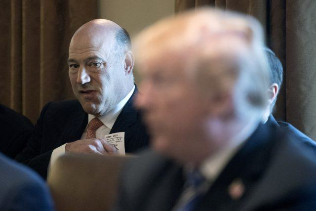 Gary Cohn puts a note in his pocket as he listens to Donald Trump