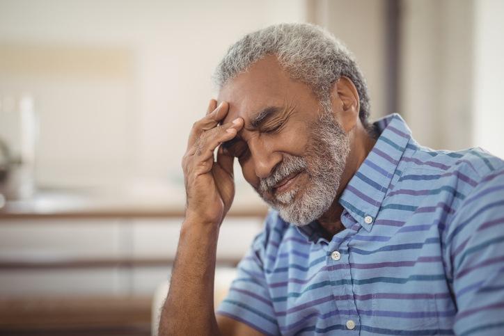 Tense senior man sitting in living room at home