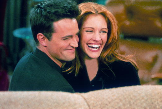 "Actor Matthew Perry and actress Julia Roberts hug each other on the set of ""Friends"""