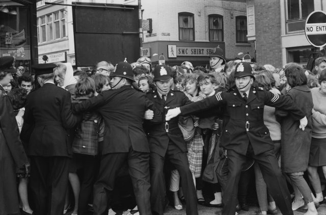 Police holding back crowds of teenagers in a queue for tickets to a Beatles concert