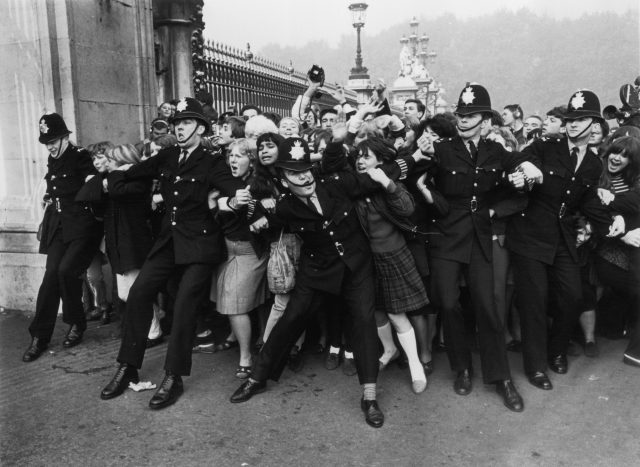 Police keeping back a crowd of young fans outside Buckingham Palace
