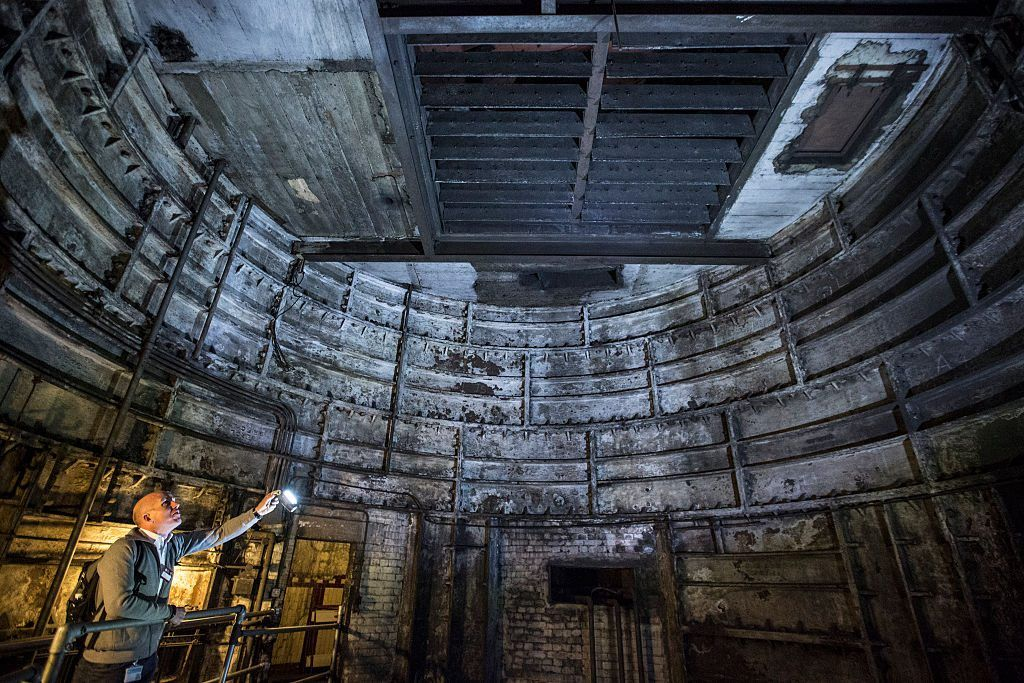A guide illuminates part of an old lift shaft inside 'Down Street' underground station on April 13, 2016 in London, England.