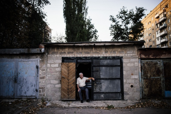 An elderly man sits in front of his garage used as a makeshift bomb shelter in Donetsk in 2014