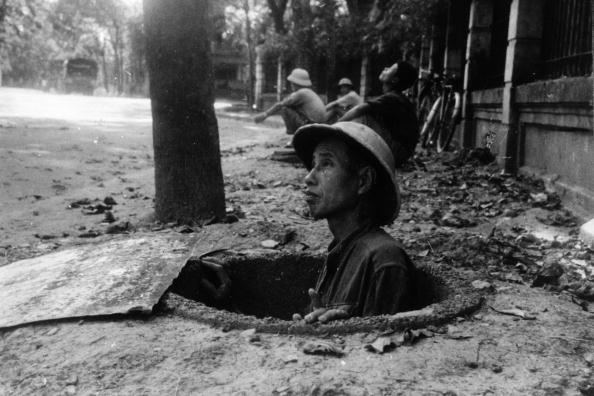 A member of the public seeks refuge in an air-raid shelter in Hanoi, while American bombers raid the city