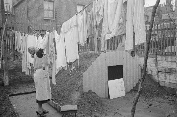 A woman hanging out her washing next to the new Anderson air raid shelter in her back yard