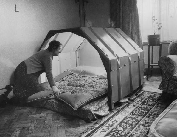 1940: A woman makes the bed in an indoor bomb shelter.