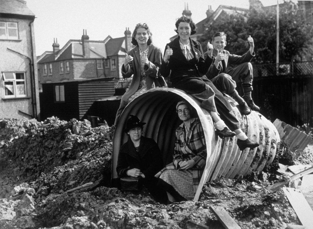 A family sitting on and in their air raid shelter