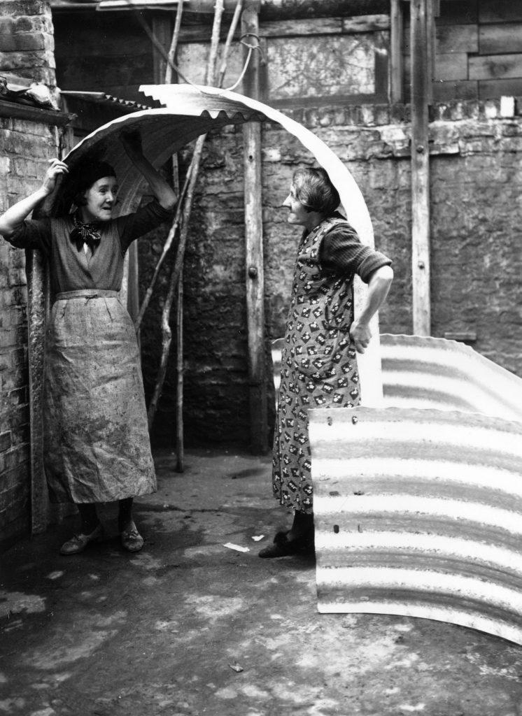 Two women in Islington, London, try out the height of their new air raid shelter