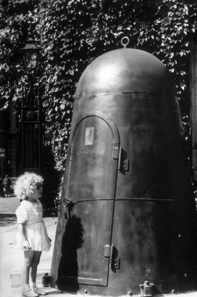 A young girl looking at the entrance to a public air-raid shelter.
