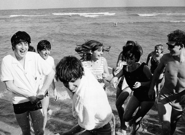 The Beatles on a beach in Miami, Florida, surrounded by female fans