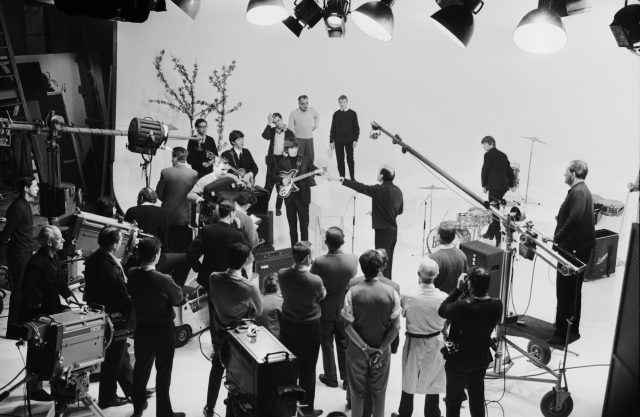 The Beatles prepare to play in a television studio