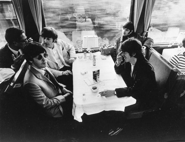 The Beatles relax in the buffet car of a train, during a tour of Europe