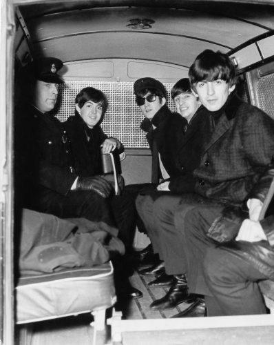 The Beatles travelling, for their own security, in the back of a police van