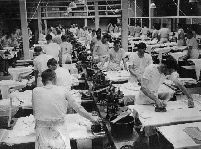 Workers iron shirts in a factory in 1925