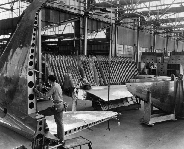 Workmen put the finishing touches to wings and tail fins at the Lockheed Corporation aircraftworks