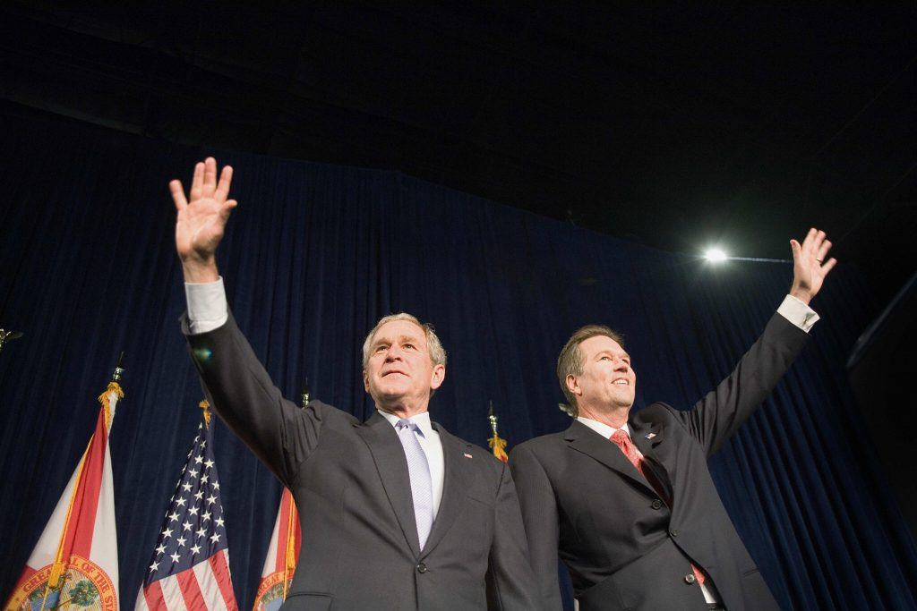George W. Bush (L) waves to the crowd with Vern Buchanan