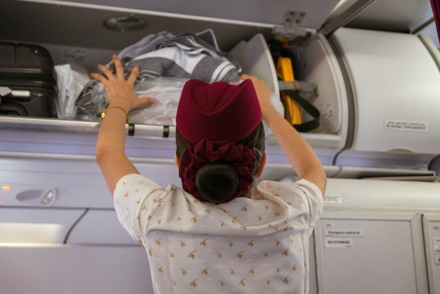 A Qatar Airways flight attendant places luggage in the overhead bin
