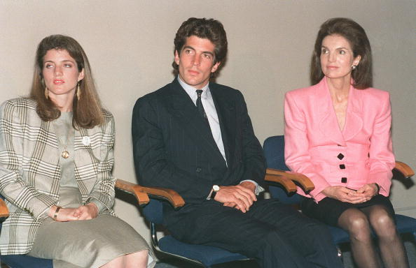 Jacqueline Kennedy Onassis sits with her children Caroline Kennedy Schlossberg and John F. Kennedy Jr during a press conference at the John F. Kennedy Library 25 May in Boston