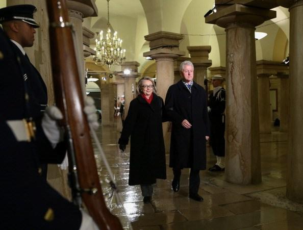 Bill Clinton and Hillary Clinton walk through the crypt