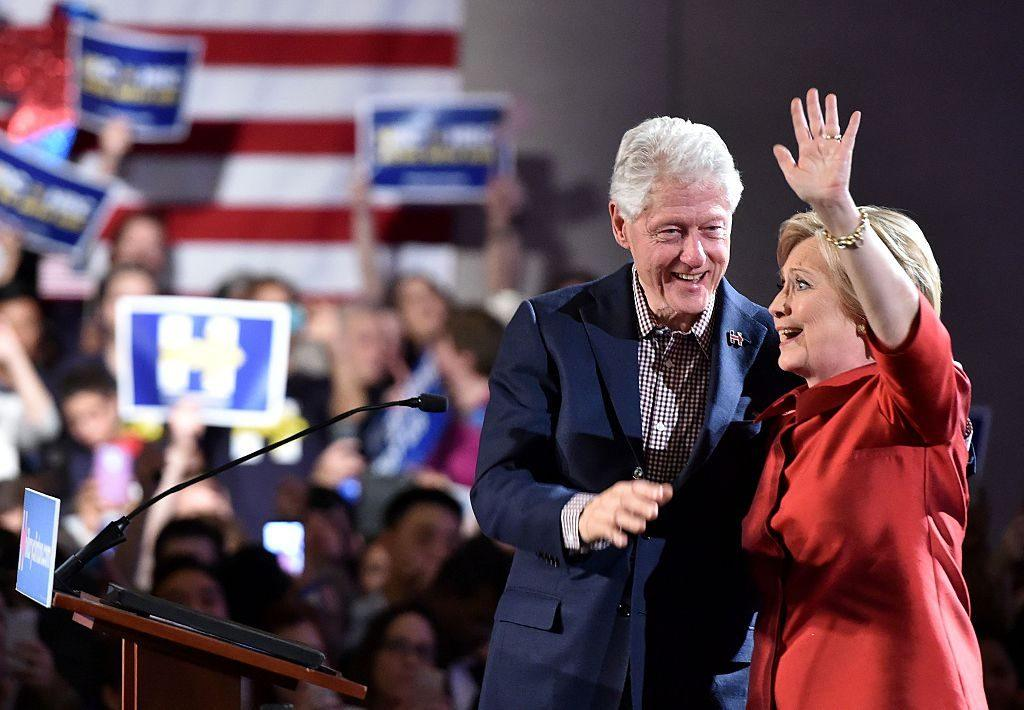 Democratic presidential candidate Hillary Clinton (R) and husband Bill Clinton (L) wave