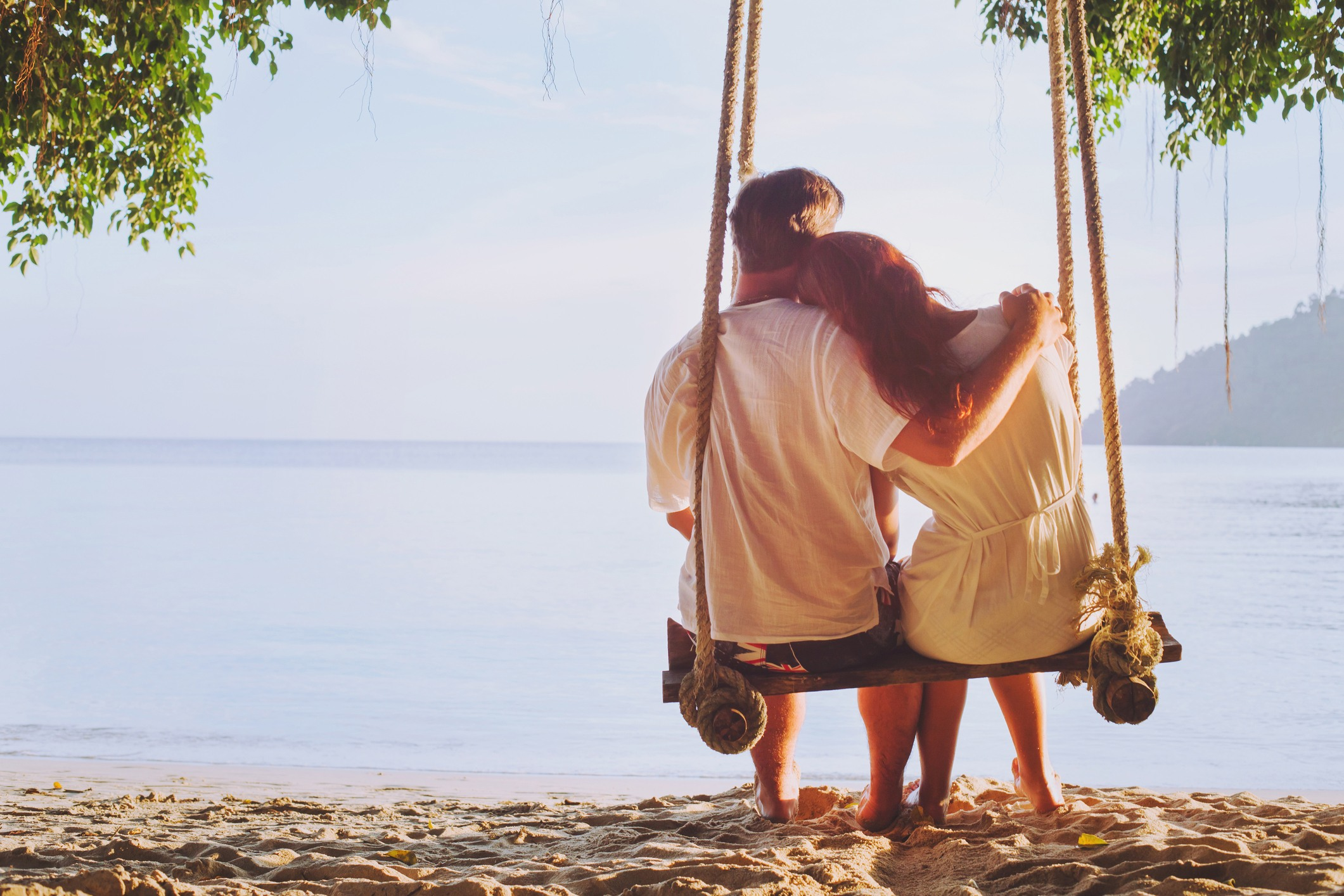 Couple sitting together on the beach on a swing