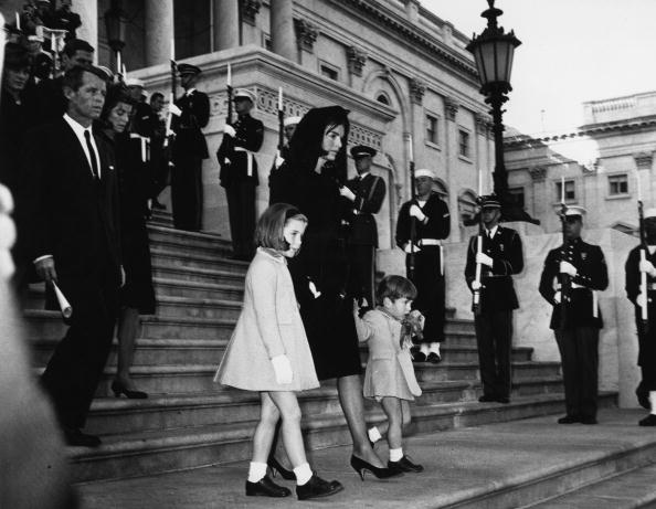 Jackie Kennedy and her children John Jr. and Caroline, walking down steps past a guard of honour at the funeral of President Kennedy. Robert Kennedy is following them