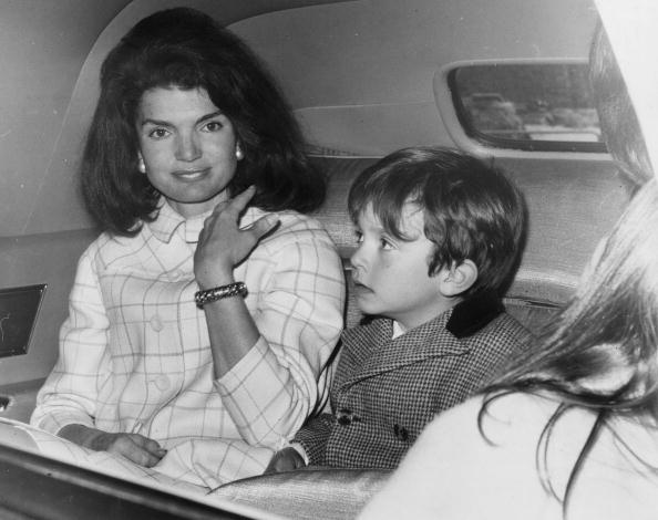 Jacqueline Kennedy in a car with one of her nephews (son of her sister, Princess Radziwill). She is stopping over in London on her way home after a visit to Spai
