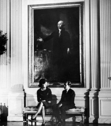 Mrs. John F. Kennedy and Charles Collingwood sit on a bench below the painting of President George Washington, during the televised tour of the White House, February 1962
