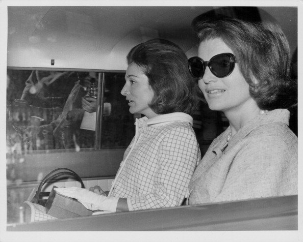 Sisters and socialites Princess Lee Radziwill and Jacqueline Kennedy, sitting in the back of a car in London, May 15th 1965