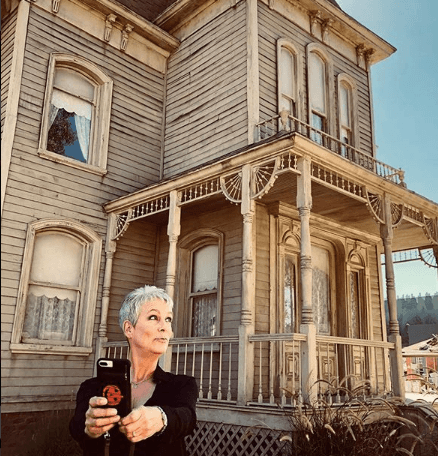 Jamie Lee Curtis in front of haunted house