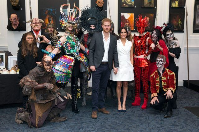 Prince Harry, Duke of Sussex and Meghan, Duchess of Sussex pose for a photo with models wearing the work of industry leading artists in film, sculpture and costume design during a visit to Courtney Creative on October 29, 2018 in Wellington, New Zealand.