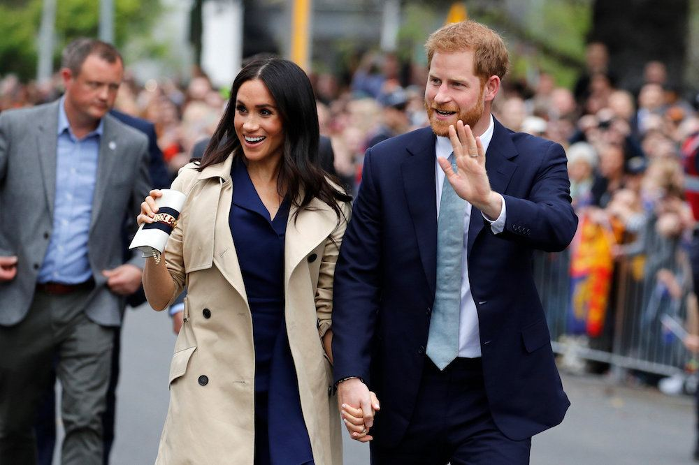 Meghan Markle and Prince Harry waving to a crowd of fans.