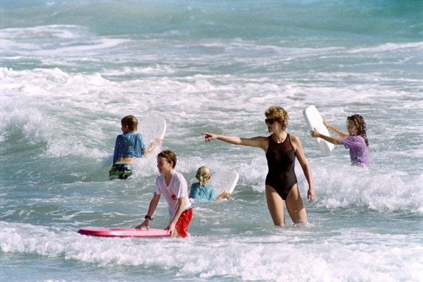 The Princess of Wales (C) heads out into the surf as her sons William and Harry enjoy the waters of Indian Castle Beach on January 1, 1993 during vacation on Nevis