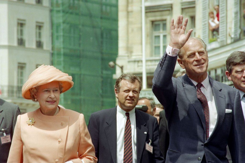 Queen Elizabeth II and Prince Philip wave as they walk to the Elysee Palace in Paris on June 9, 1992
