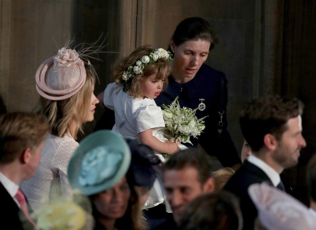 Royal Nanny Maria Teresa Turrion Borrallo comforts bridesmaid Zalie Warren inside the entrance to the chapel before the wedding of Prince Harry to Meghan Markle in St George's Chapel at Windsor Castle on May 19, 2018 in Windsor, England