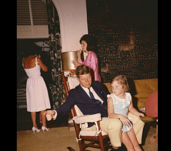 Easter Sunday 1963. President Kennedy sits with his daughter while Jackie Kennedy steals a smoke behhind them.