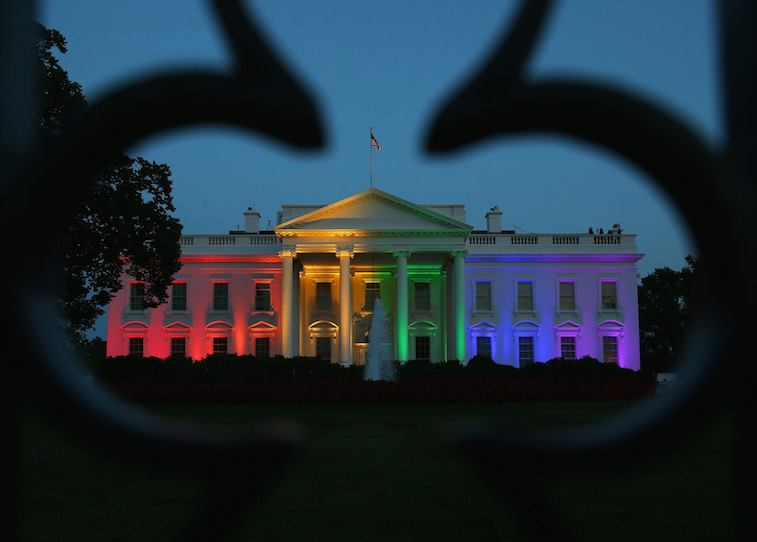 Rainbow-colored lights shine on the White House