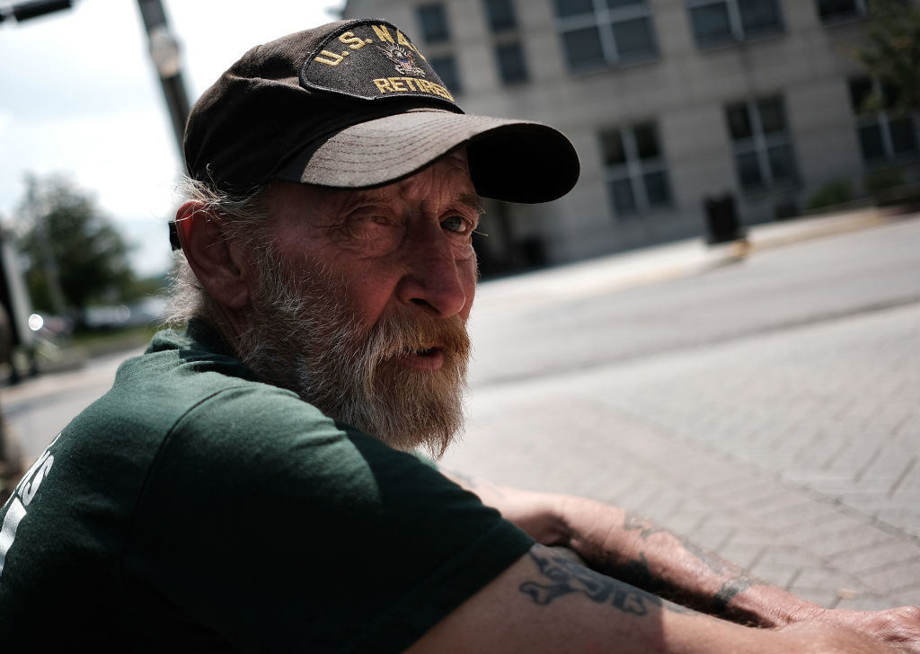 A homeless veteran sits on the streets