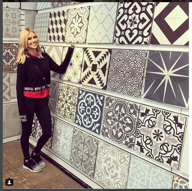 Christina El Moussa standing next to design tiles