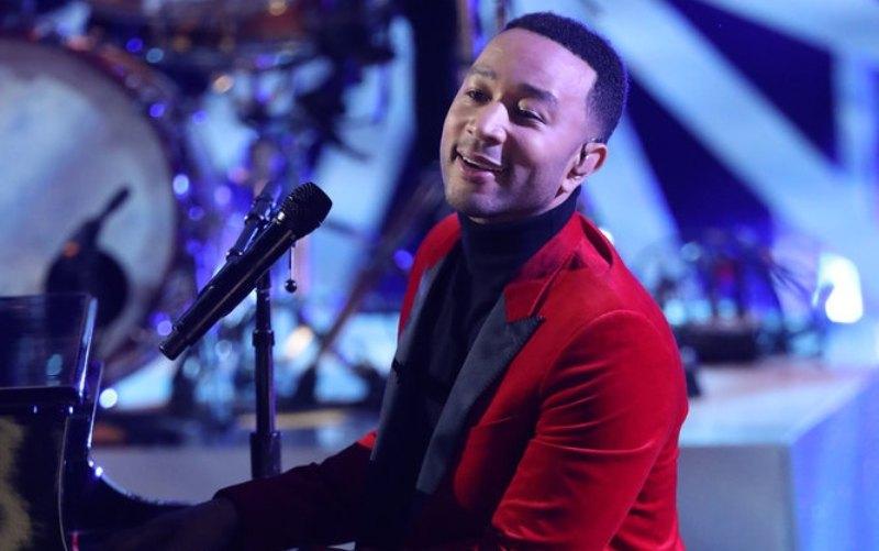 John Legend behind a piano
