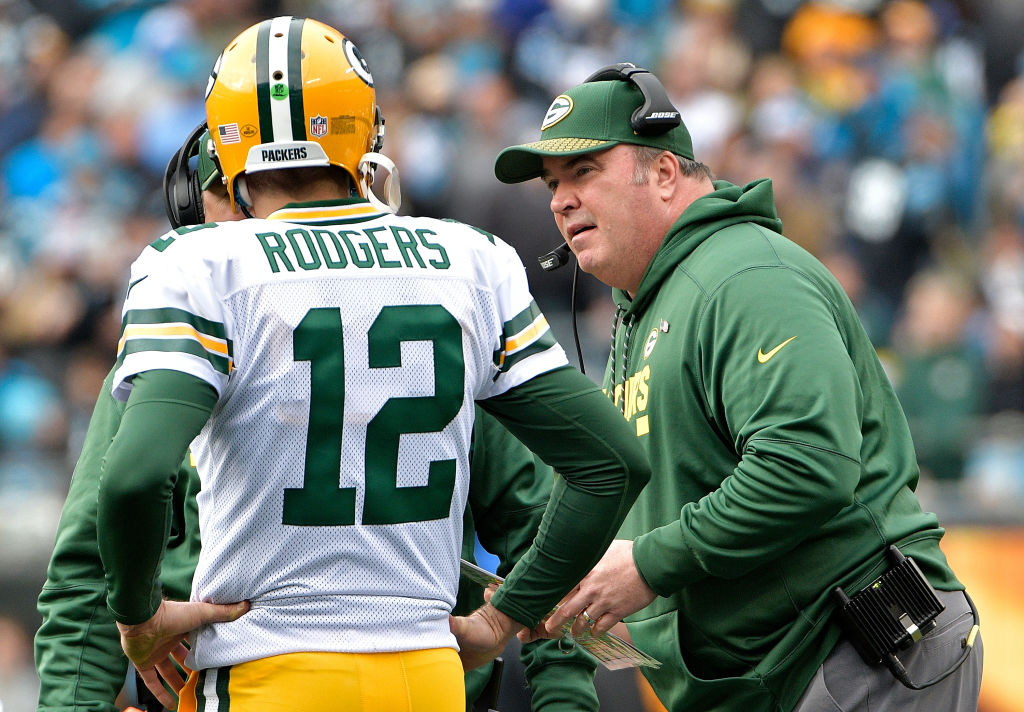 Head coach Mike McCarthy talks to Aaron Rodgers of the Green Bay Packers in the second quarter against the Carolina Panthers at Bank of America Stadium on December 17, 2017 in Charlotte, North Carolina.