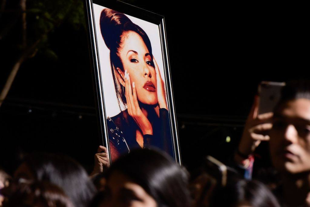 A fan holds up a photo of Selena Quintanilla