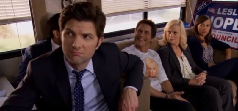 Parks and Recreation cast are sitting in a bus.