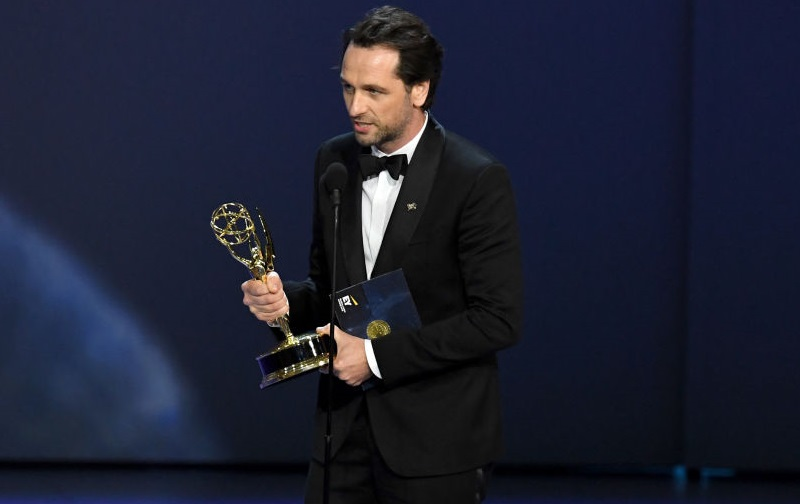 Matthew Rhys wearing a black tuxedo, holding an Emmy award, and speaking into a microphone.